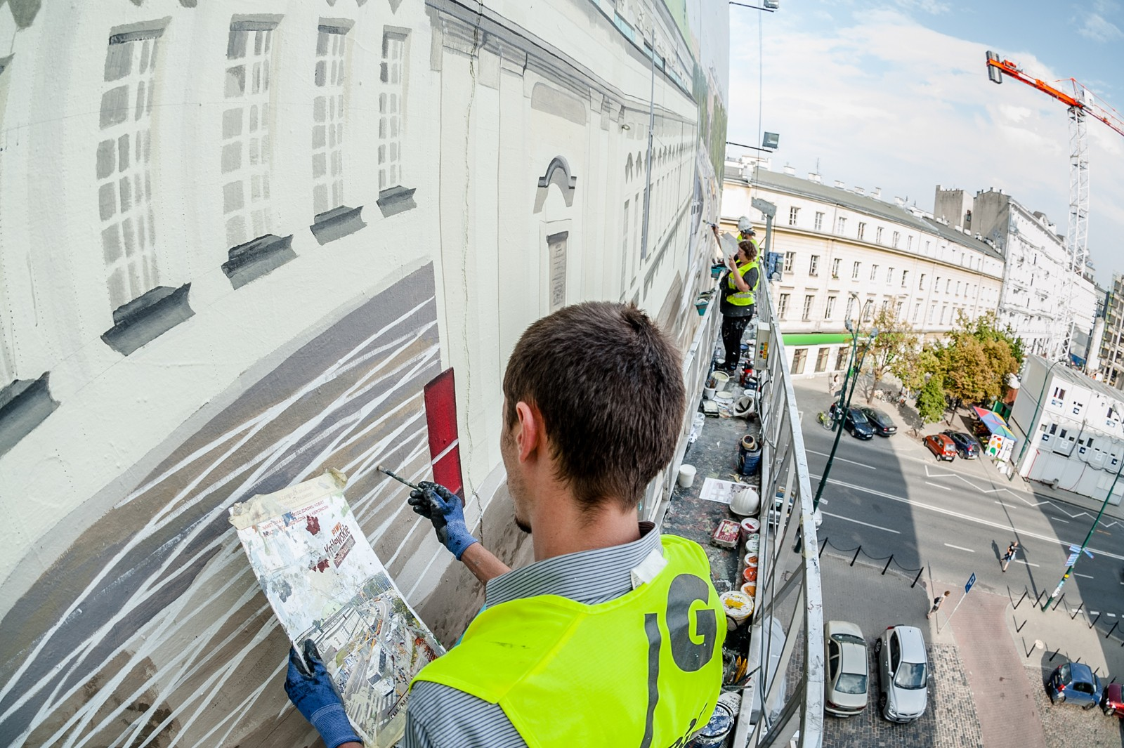 Artist at work painting a mural on a wall at 25 Bracka street in Warsaw city centre | Krolewskie unfiltered | Portfolio