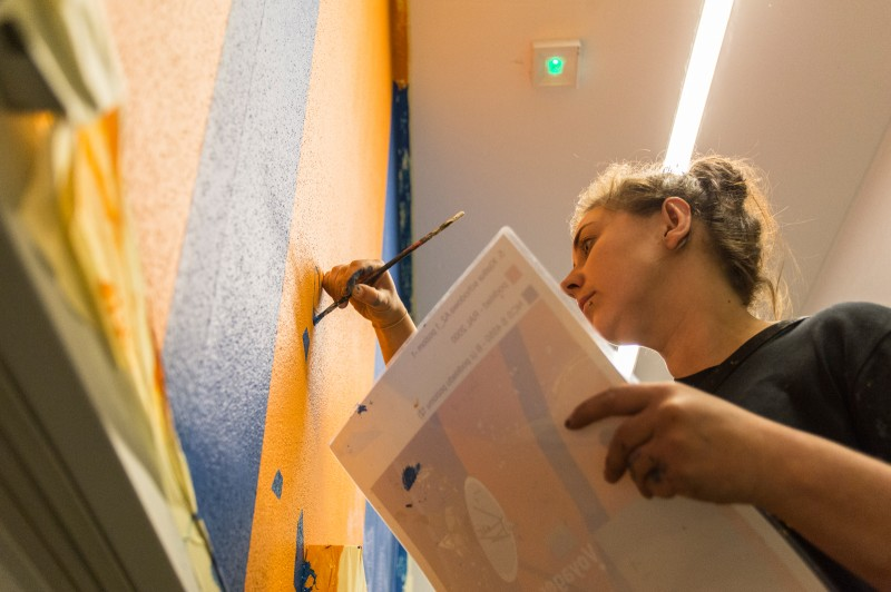 Artist painting wall designs in a modern Proximo office building on Przyokopowa street in Warsaw | PROXIMO | Portfolio