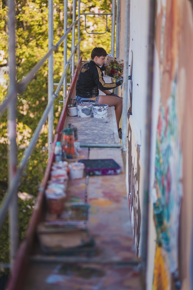 Painter on the scaffolding while working on the basis of the mural | Gardena | Portfolio