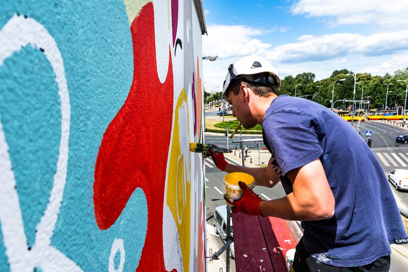 The artist paints an advertising mural for Naked on Francuska street | #PowerFullCity | Portfolio