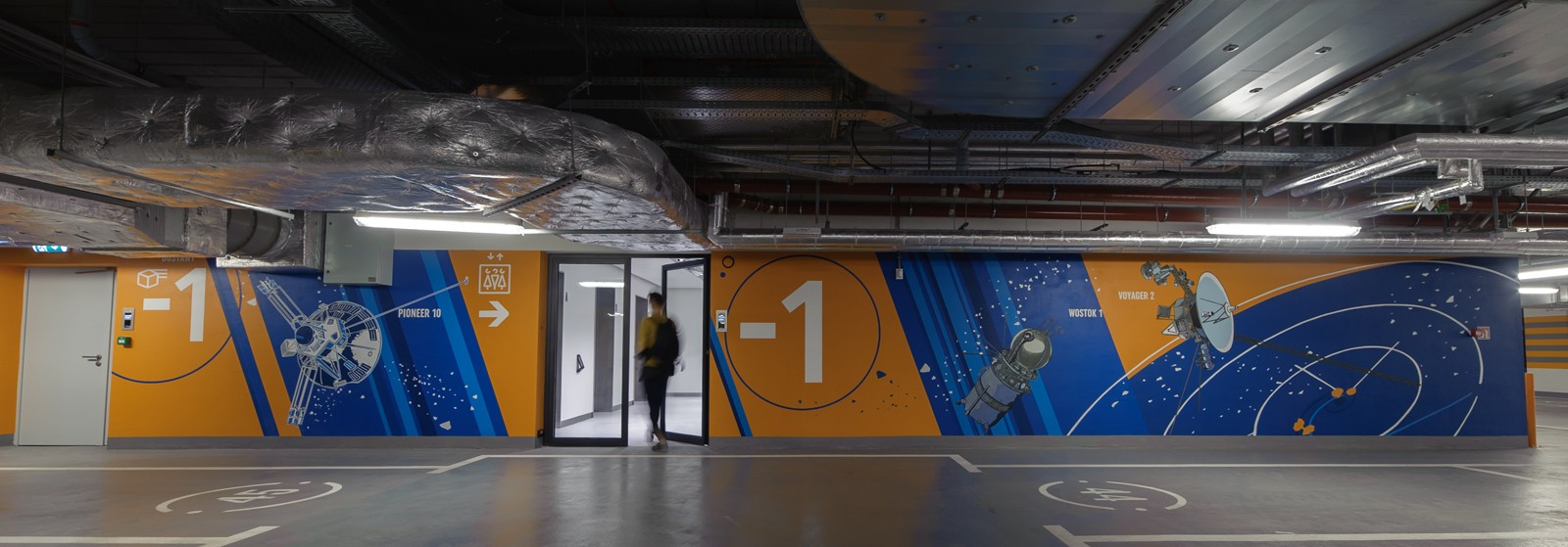 Wall design in Proximo office building in Warsaw's Wola district with a painted Pioneer 10 satellite, a Wostok 1 spaceship, and a Voyager 2 space shuttle | PROXIMO | Portfolio