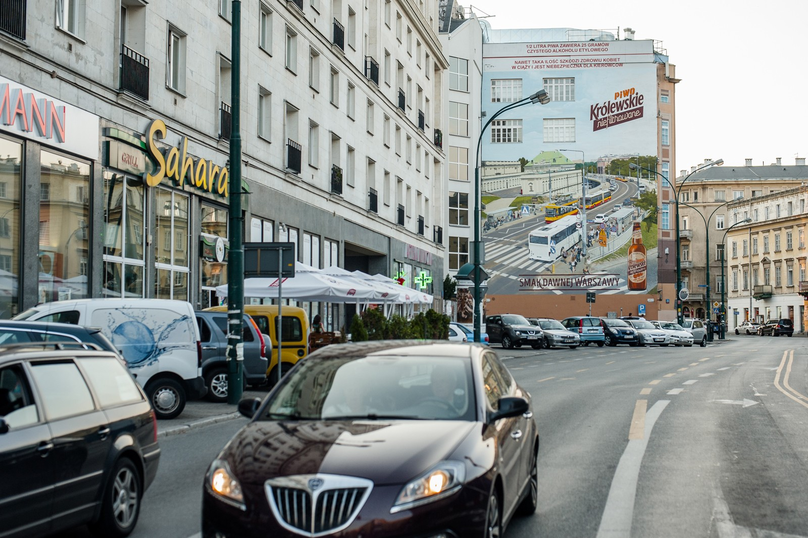 A view on Krucza street in Warsaw with an advertising mural of Krolewskie unfiltered beer in the background | Krolewskie unfiltered | Portfolio