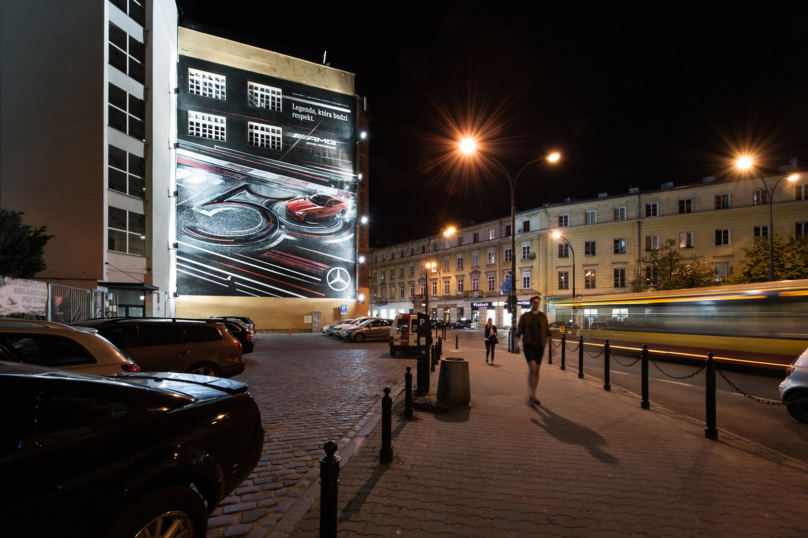 A night view from Krucza street on Dom Towarowy Bracia Jablkowscy located at 25 Bracka street in Warsaw with a hand painted mural for Mercedes Benz Polska | Mercedes AMG | Portfolio