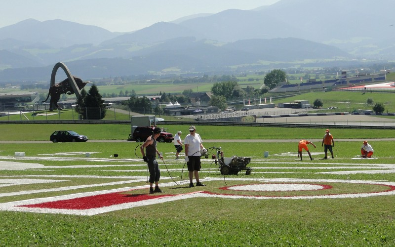Painting the logotype on grass at formula 1 race track in Spielberg - Austria | branding miejsc na zlecenie RedBull | Portfolio